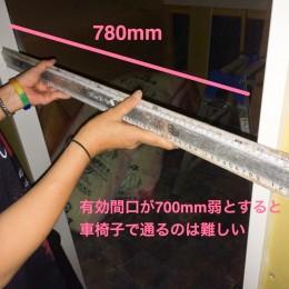 店舗改装工事中にトイレのドア接地部分に大きな定規を当ててEVAが長さを測っている様子。780ミリメートルしかないことがわかる。有効間口が700ミリメートル弱だと思われるため、車椅子で通るのは難しいのがわかる。