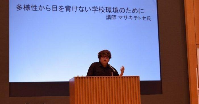 マサキが登壇している講演会の様子、背景には「多様性から目を背けない学校環境のために」とある。